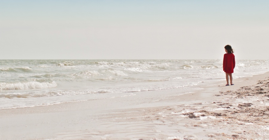 a little girl standing on the shore looking out over the ocean